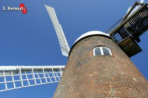 Old windmill against blue sky background